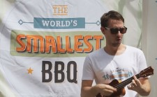 A mandolin player in front of a sign saying The world's smallest bbq